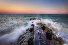 Waves and a jetty at sunset in the Atlantic Ocean at Edisto Beac Royalty Free Stock Photos