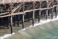 Waves just beginning to break against wood pilings of an ocean pier, Santa Monica CA Royalty Free Stock Images