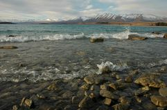 Waves at lake. Waves hitting the shore of a lake with mountains behind Stock Photography