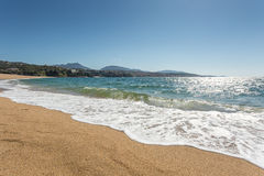 Waves lapping the beach at Propriano in Corsica. Waves gently lapping onto the beach at Propriano with golden sand, blue sea and blue sky and hills in the Stock Photos