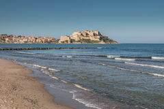 Waves lapping onto Calvi beach with Citadel and town behind Royalty Free Stock Photo