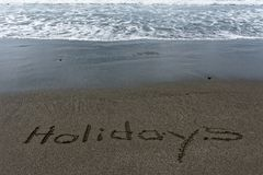 Holidays written in the sand on the beach royalty free stock photography