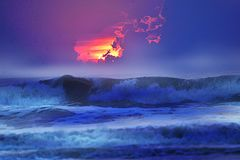 Sunrise arrives with the fog low on the ocean waves below royalty free stock image