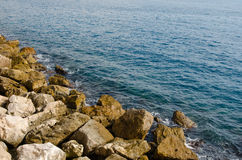 Waves of the mediterranean sea water crushing into reddish rocks Stock Photo