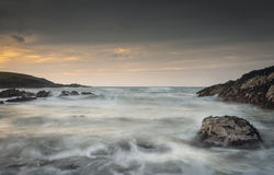 Waves in Motion. Waves swirl around the weed covered rocks in this small but exposed bay on the North Wales coastline Stock Image