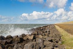 Waves near a Dutch breakwater with Windturbines Royalty Free Stock Images