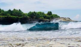 Waves at Nusa lembongan beach. Bali. Wates plash. ROcks. Green trees.n royalty free stock image