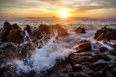 Waves of the ocean beat against the rocks, sunset Stock Image