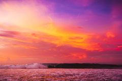 Waves in ocean at bright pink sunset or sunrise. Ocean with warm sunset colors. Waves in ocean at bright pink sunset or sunrise. Ocean with warm sunset Stock Image