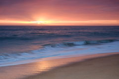 Waves onto the shore during late afternoon Stock Image