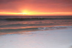 Waves onto the shore during sunset Stock Photo