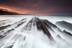Waves over the flysch at sunset Stock Photo