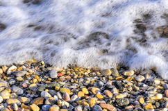 Waves over pebbles, Turkey. Close up of waves washing over colorful pebbles in Datca, Turkey Royalty Free Stock Image