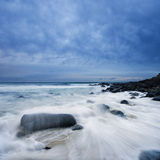 Waves over rocks on cloudy morning Royalty Free Stock Image