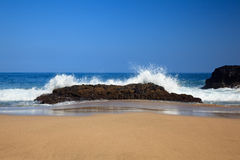 Waves over rocks on Lumahai. Strong waves crash over rocks on the beach at Lumahai on Kauai stock images