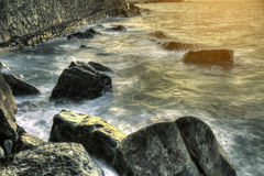 Waves over rocks at sunset on the bay of biscay beach in spain Royalty Free Stock Images