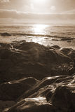 Waves over sepia sunset rocks Stock Image