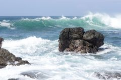 Waves crash onto volcanic rocks. Stock Images