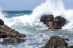 Waves crash onto volcanic rocks. Royalty Free Stock Photography