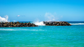 Waves of the Pacific Ocean crashing on the rocks of the barriers at the man made lagoons on the shoreline of Ko Olina. On the island of Oahu in the island Stock Photography
