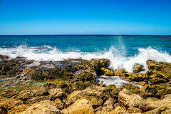 Waves of the Pacific Ocean crashing on the rocks on the shoreline of Ko Olina. On the island of Oahu in the island state of Hawaii Royalty Free Stock Image