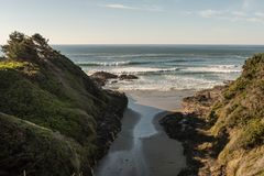 Waves of the Pacific Ocean and an entrance of sand between green hills in Cape Perpetua stock photo
