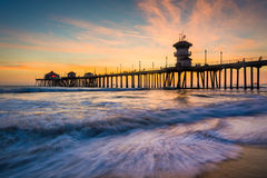 Waves in the Pacific Ocean and the pier at sunset. In Huntington Beach, California stock image