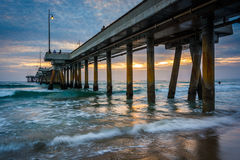 Waves in the Pacific Ocean and the pier at sunset  Stock Images