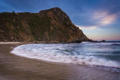 Waves in the Pacific Ocean and a rocky bluff at Pfeiffer Beach  Stock Photos