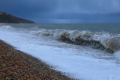 Waves on a pebble beach. Near town of Seaton in Devon on the Jurassic Coast royalty free stock image