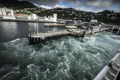 Waves at Port of Ships in New Zealand  d.y. Stormy waters at the harbor of ships in New Zealand Royalty Free Stock Images