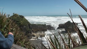 Waves and power water on a rocky coast and mountains New Zealand. stock footage