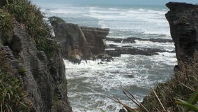 Waves and power water on a rocky coast and mountains New Zealand. stock video footage