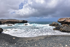 Waves Receding on the Black Pebble Beach in Aruba Stock Photography