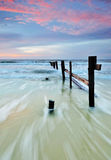 Waves with Remnant of wooden jetty at Sunset Stock Photo