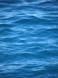 Waves and ripples on blue sea. Reflection and waves on blue clear Adriatic sea (Croatia-Dalmatia). Vertical color photo Royalty Free Stock Image