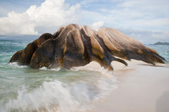 Waves and a rock formation on a beach Royalty Free Stock Image