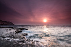 Waves, rock and sun Stock Images