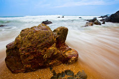 Waves and rocks. Waves rushing through rocks on a beach. Captured in Kijal, Trengganu, Malaysia Royalty Free Stock Photography