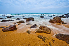 Waves and rocks. Waves flowing through rocks on a beach in Kijal, Trengganu, Malaysia Royalty Free Stock Photography