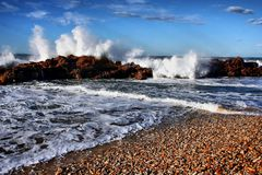 Waves and Rocks. Dramatic shoreline with crashing waves, rocks and pebbles Royalty Free Stock Images