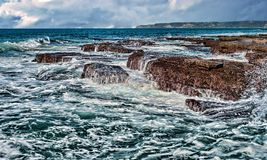 Waves on rocks at the coast Royalty Free Stock Photography