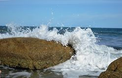Waves in the rocks. Waves crashing on the rocks, in the beach Stock Photo