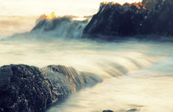 Waves on the rocks. Cross process Stock Images