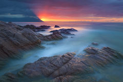 Waves and rocks in motion blur on coastline at dawn Stock Images