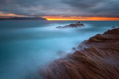 Waves and rocks in motion blur on coastline at sunrise