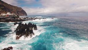 Waves and rocks near city and pools of Porto Moniz aerial view stock video footage