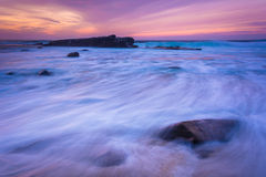 Waves and rocks in the Pacific Ocean at sunset  Stock Photos