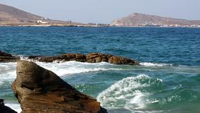 Waves on rocks. Waves splashing on sea shore with mountains on the background stock video