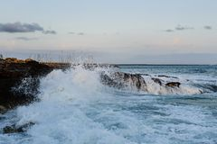 Waves and rocky shore. Big sea waves breaking at rocks. Evening warm lighting Royalty Free Stock Photos